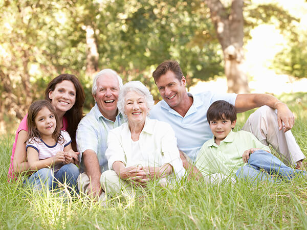 A family with two children and their grandparents sitting on the grass in a park while smiling and hugging