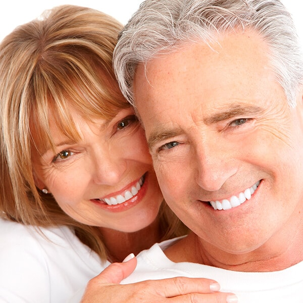 A mature woman hugging her husband while they both smile at the camera