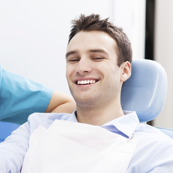Young man sitting in a blue dental treatment chair smiling with his restorative dentist