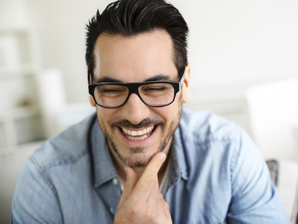 Man with dark hair and glasses looking down smiling resting his chin in his hand with a blurry background