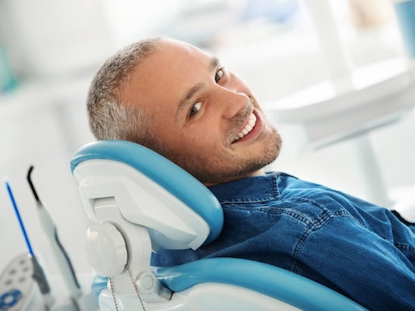 Man in a denim shirt reclining on a dental chair looking back at his dentist