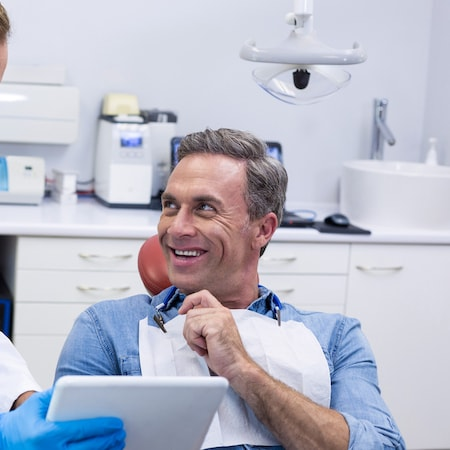 A man looking at his dentist to his right smiling with his hand touching his chin