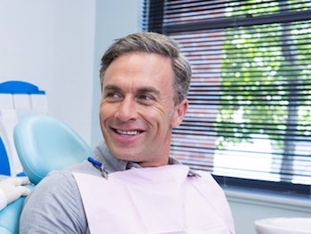 Mature man sitting in a dental chair looking to his right as he waits to enjoy our services