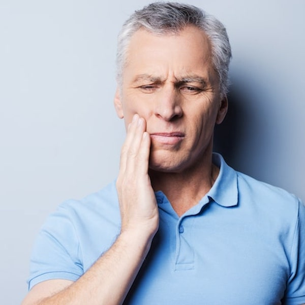 A man in a light blue top holding the side of his face in pain due to a TMJ disorder