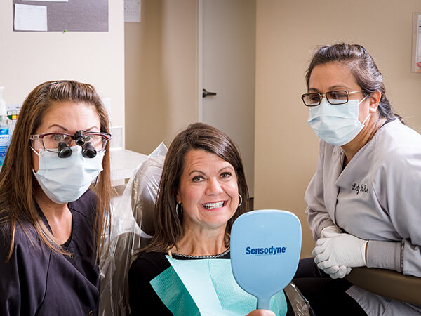 A female patient with a handheld mirror smiling with her dentist and dental hygienist